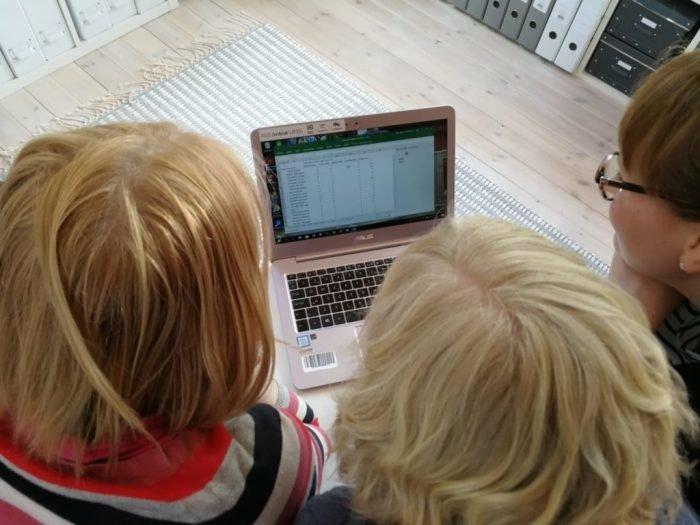 Kolme tutkijaa katsovat yhteistä tietokoneennäyttöä.