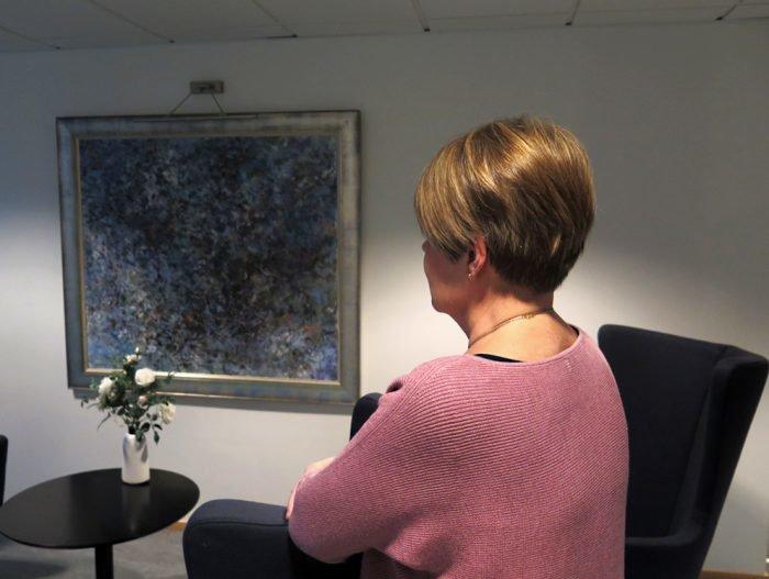 Marianne katsoo eteenpäin, niin että me näemme hänestä vain sivuprofiilin. Pöydällä on kukkia, seinällä tummasävyinen taulu.