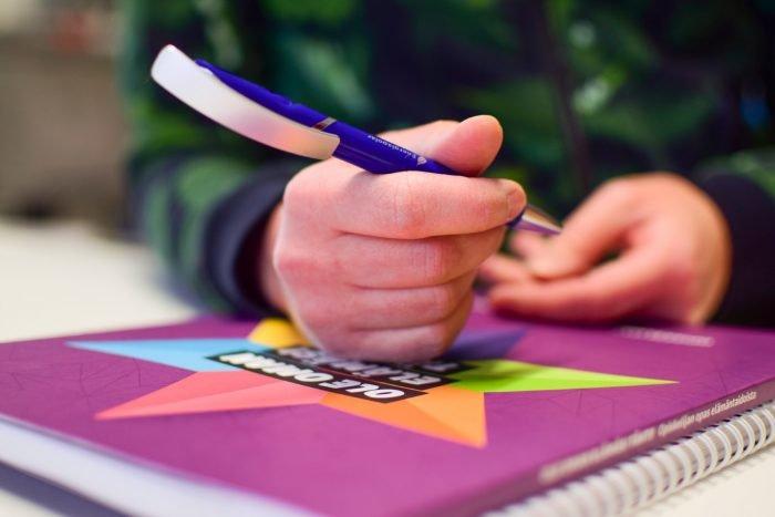 Kuvassa on käsi, jossa on kynä. Käsi lepää vihkon päällä.