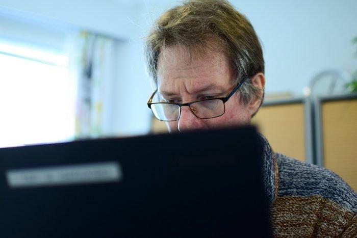 Mies istuu tietokoneen takana keskittynyt ilme kasvoillaan.