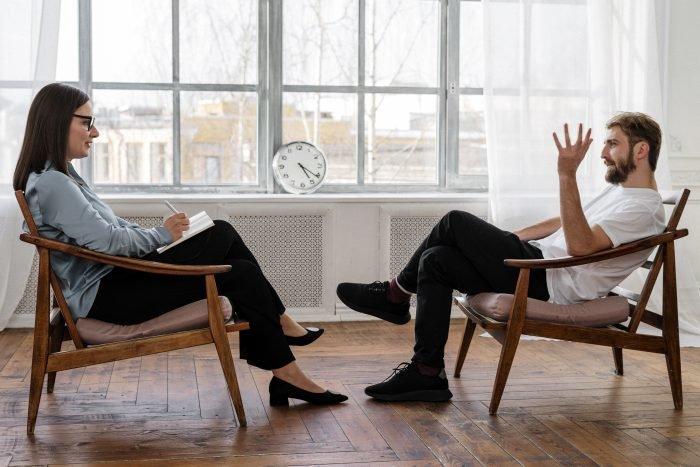 Kuvassa mies ja nainen keskustelevat. Taustalla on suuri kello.